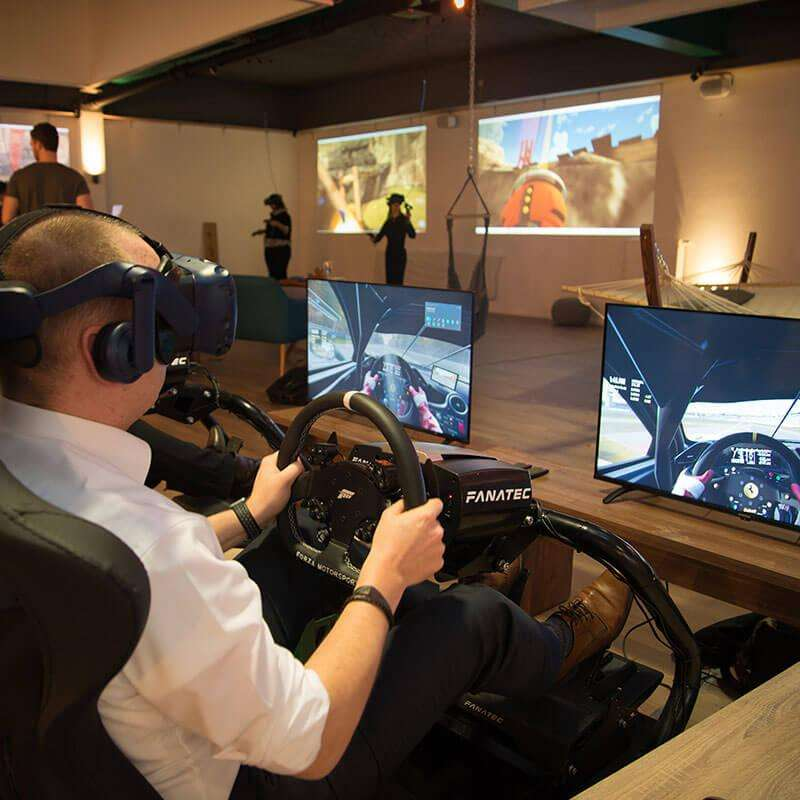 Ein Mann sitzt mit einer Virtual Reality Brille in einem Rennsitz und spielt einen Rennsimulator.