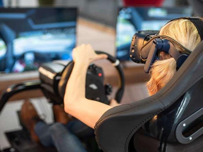 Eine junge Frau mit Virtual Reality Brille liefert sich ein spannendes Autorennen.