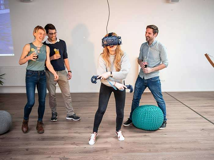 Eine Gruppe von Freunden steht um eine junge Frau mit Virtual Reality Brille herum und freut sich.
