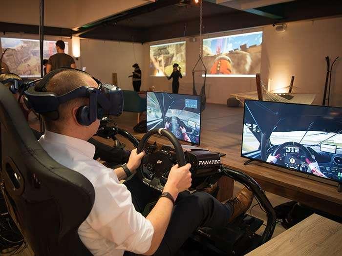 Ein Mann mit Virtual Reality Brille sitzt in einem Rennsitz und fährt ein Rennen gegen seinen Freund.