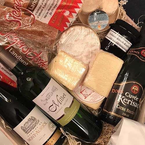 Auf diesem Bild sieht man ausgewählte Käse-, Brot- und Weinspezialitäten vom Käse Langer Fürth.