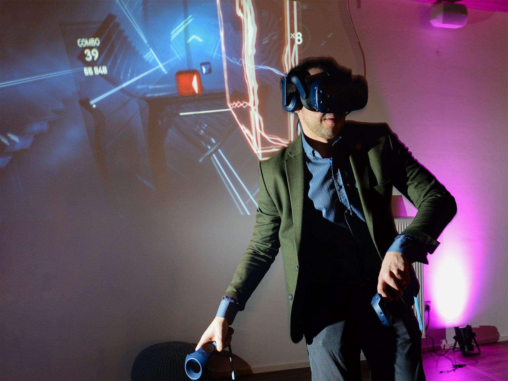 Foto von einem Mädchen mit einer Virtual Reality Brille, das von lachenden Freunden umgeben ist.