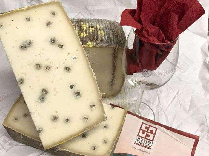 Hier sieht man leckeren Käse neben einem Weinglas